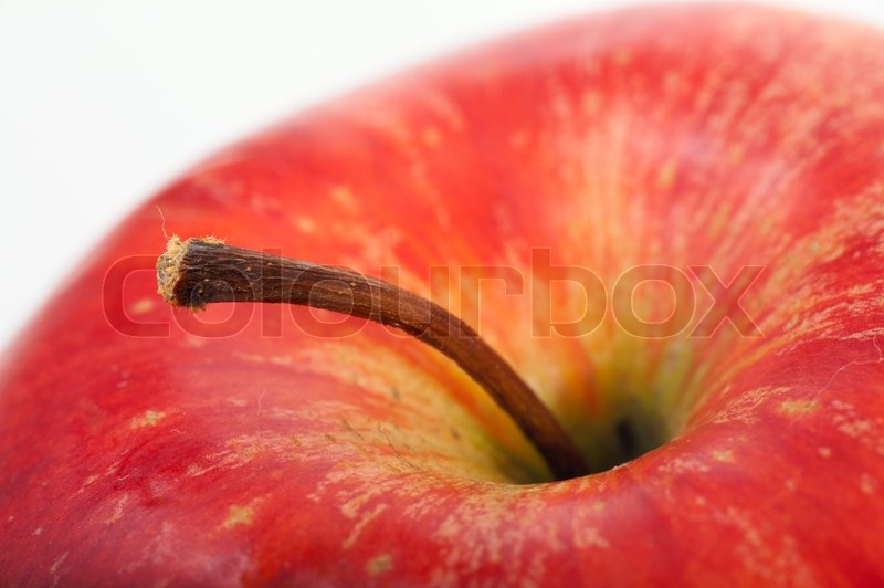 Stock image of 'Closeup part of big red apple with stem on light background (not isolated)'