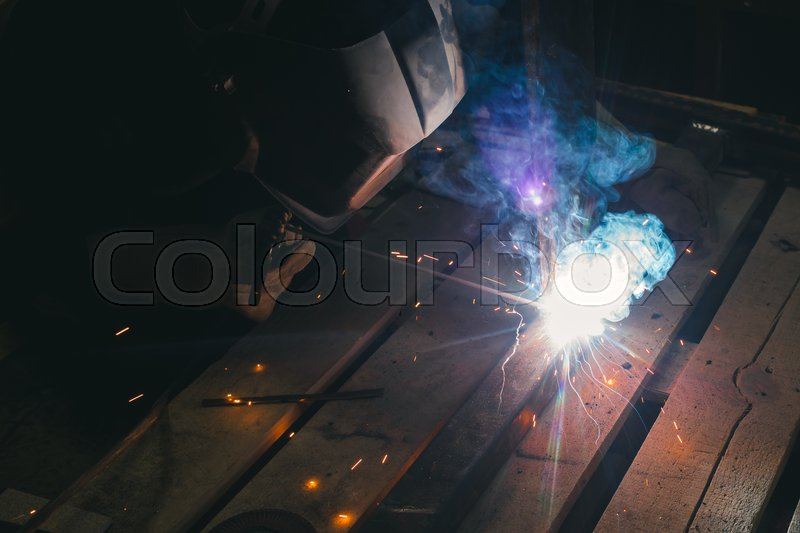 Worker with personal protective equipment and protective mask welding steel pipe in factory, stock photo