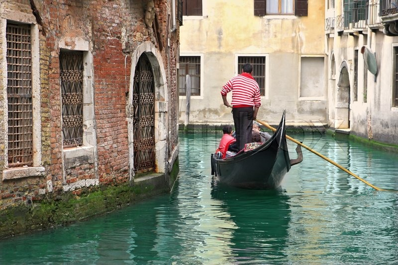Venetian canal and gondola among old houses in Venice, Italy | Stock Photo | Colourbox
