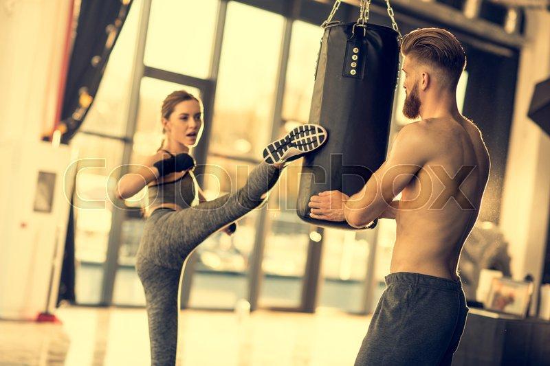 Young sportswoman kicking punching bag in sports center, stock photo