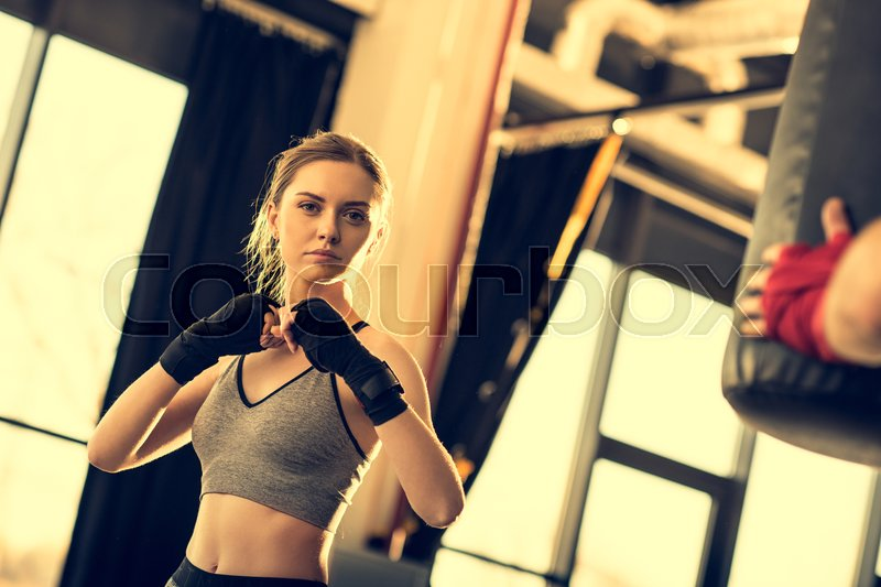 Young attractive sportswoman with punching bag in sports center, stock photo
