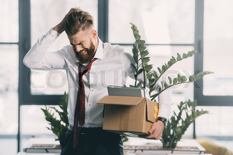 Young upset fired businessman with cardboard box in office, stock photo