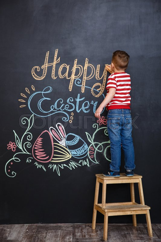Little boy drawing easter doodles on chalk black board while standing on the ladder, stock photo