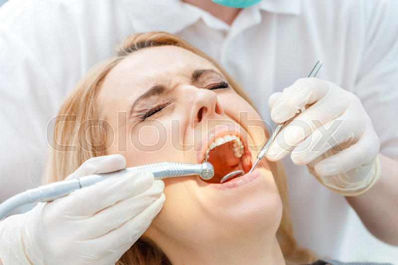 Close Up Partial View Of Dentist Curing Scared Patient With Closed Eyes