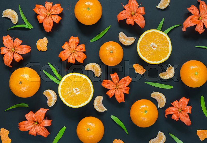 Pattern with lily flowers, oranges and mandarines on black background. Flat lay, top view, stock photo
