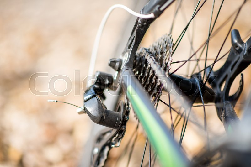 Close-up view of rear wheel of bicycle with chain and sprocket on blurred autumn leaves background, stock photo