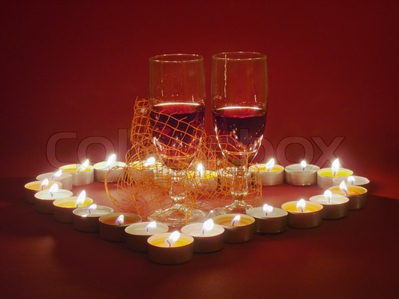 romantic valentine day composition with two glass of red wine in the center of candle burn heart on red background make specially some dark as a - Valentine Wine Glasses