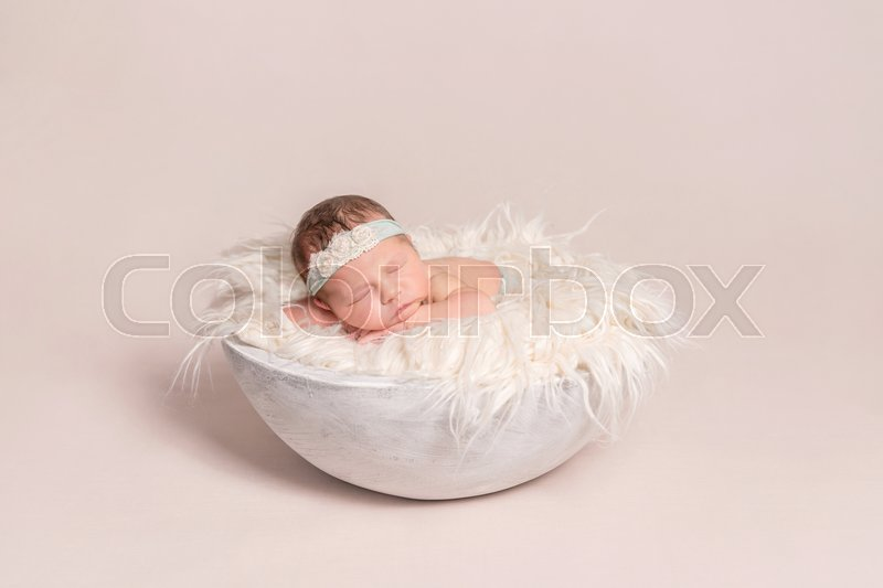 Lovely baby girl napping on the huge soft pillow, wearing hairband decorated with flowers, stock photo