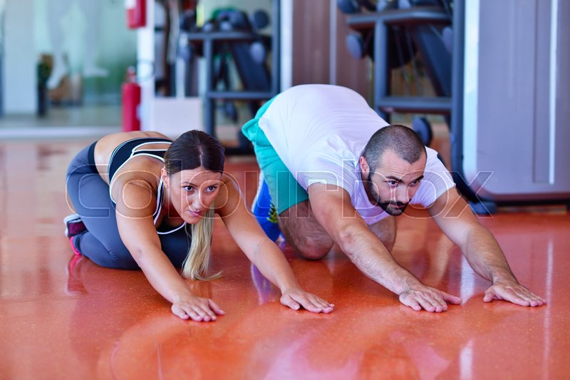 Young people involved in sports. Woman stretching with personal trainer, stock photo