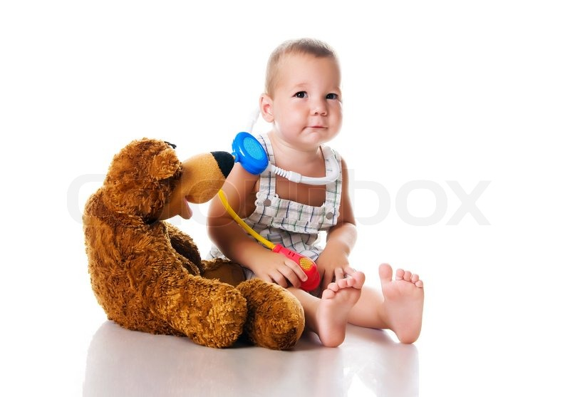 Stock image of 'Little boy playing doctor with a teddy bear - studio shot - isolated'