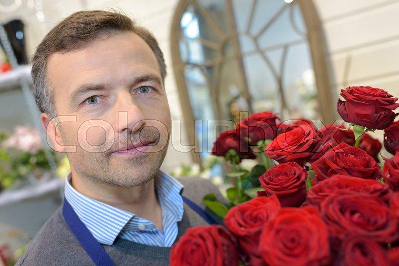 Portrait of male florist holding roses, stock photo