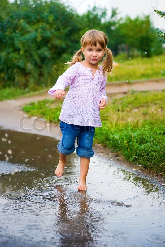 Girl Junps Barefoot In A Puddle Splashing Water In The
