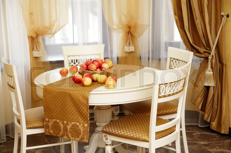 Table with apples and chairs in the beautiful room, stock photo