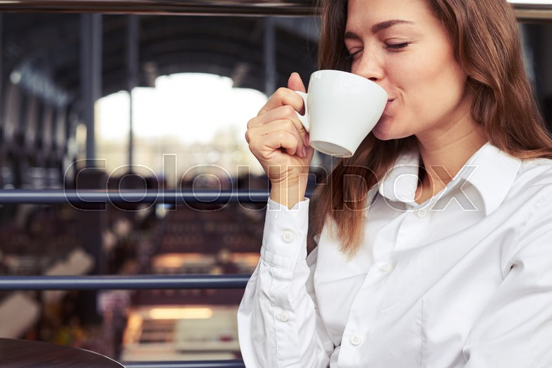 Close-up of very nice woman in white shirt tasting cup of espresso in café, stock photo