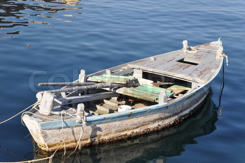 Old Wooden Fisher Boat Tied To Buoys Not Visible In A