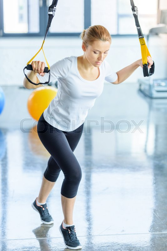 Blonde sportswoman training with resistance band in sports center , stock photo