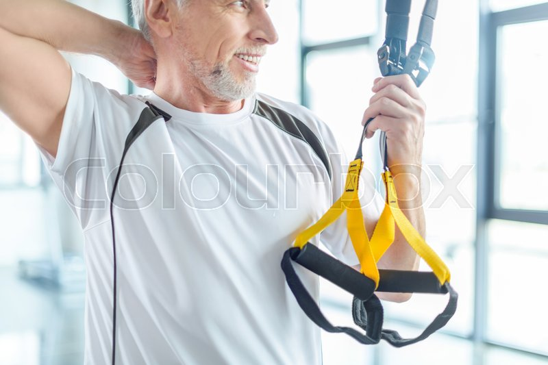 Senior sportsman training with resistance band in sports center , stock photo