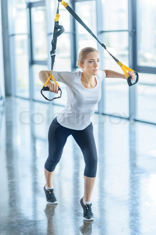 Concentrated sportswoman training with resistance band in sports center, stock photo