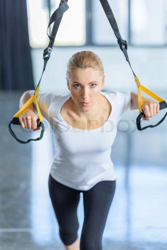 Concentrated sportswoman training with resistance band in sports center , stock photo
