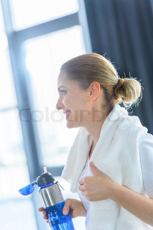 Sportswoman with towel holding sport bottle in sports center , stock photo