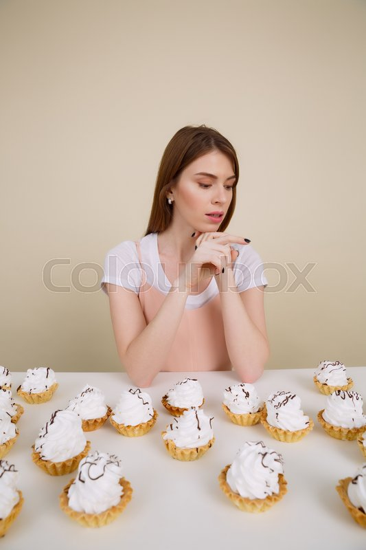 Vertical image of sensual woman sitting by the table with many cakes while looking away over cream background, stock photo