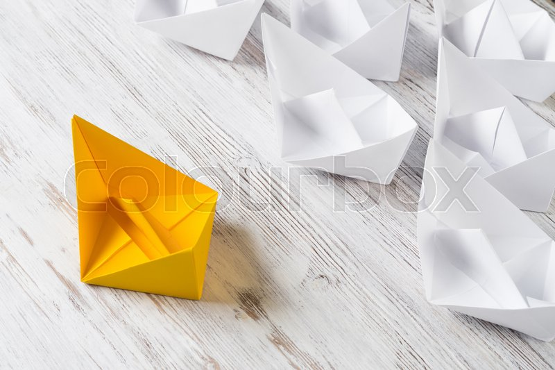 Business leadership concept with white and color paper boats on wooden table, stock photo