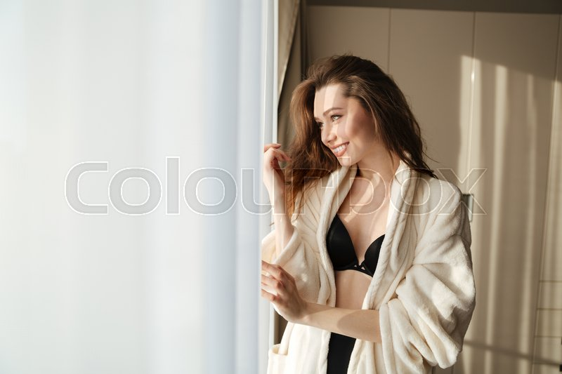 Stock image of 'Smiling attractive young woman in lingerie and bathrobe standing near the window at home'