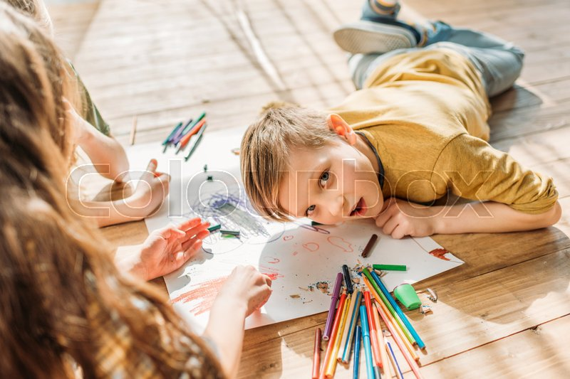 Cute kids drawing on paper with pencils while lying on floor, stock photo
