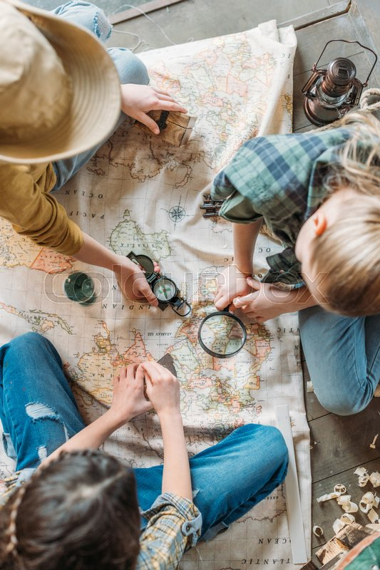 Cute kids playing treasure hunt with map on porch, stock photo