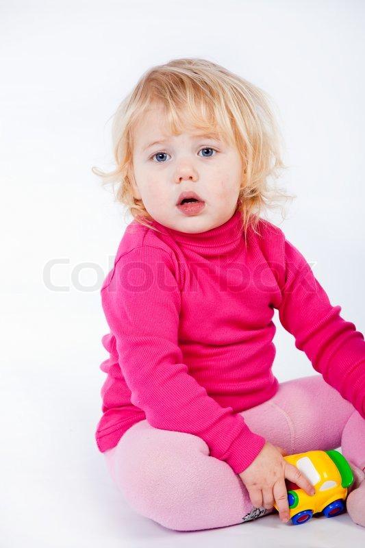 Baby mädchen mit einem spielzeug auf weißem stockfoto