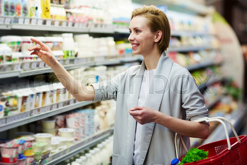 Stock image of 'Young woman choosing fresh milk in supermarket'