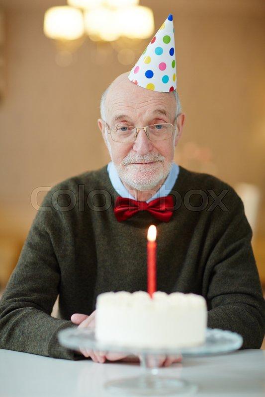 Sad senior man sitting by table with birthday cake, stock photo