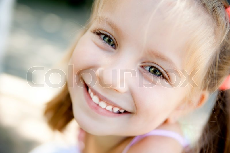 Cute little girl smiling in a park close-up, stock photo