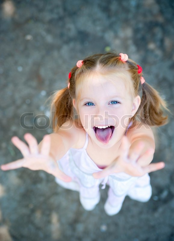 cute little girl smiling in a park close up stock photo colourbox