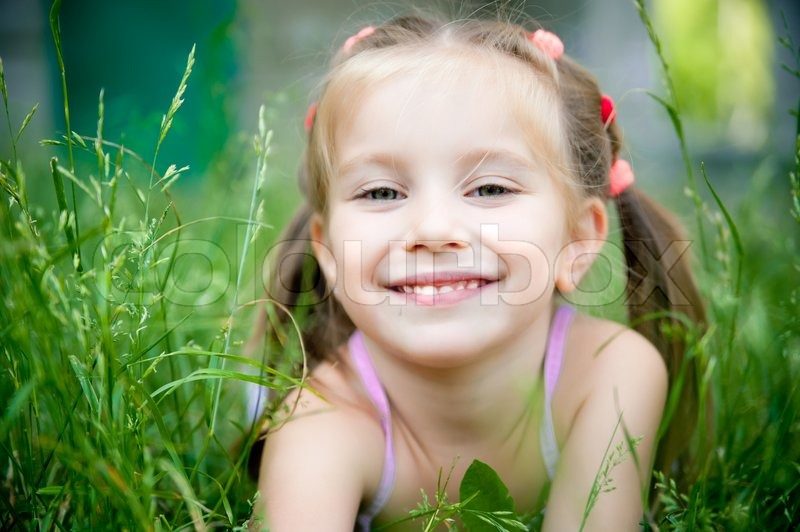 Cute Little Girl Smiling In A Park Close Up Stock Photo