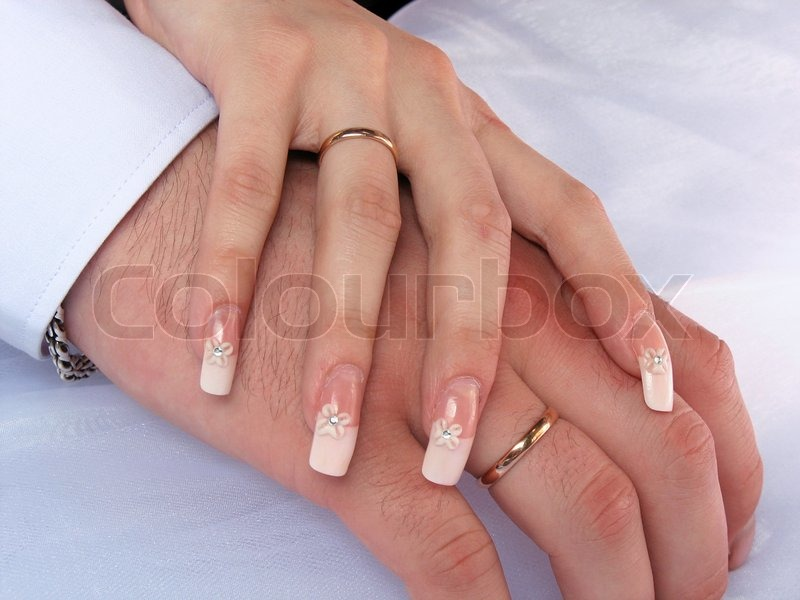 Hands of a man and woman with wedding rings stock photo What finger to wear a ring on female
