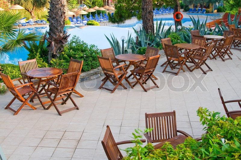 Hotel Patio With Tables And Chairs Next To Swimming Pool Stock Photo Colourbox