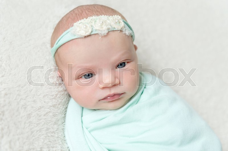 Lovely kid with eyes wide open wrapped up, blue hairband on her head, topview, stock photo