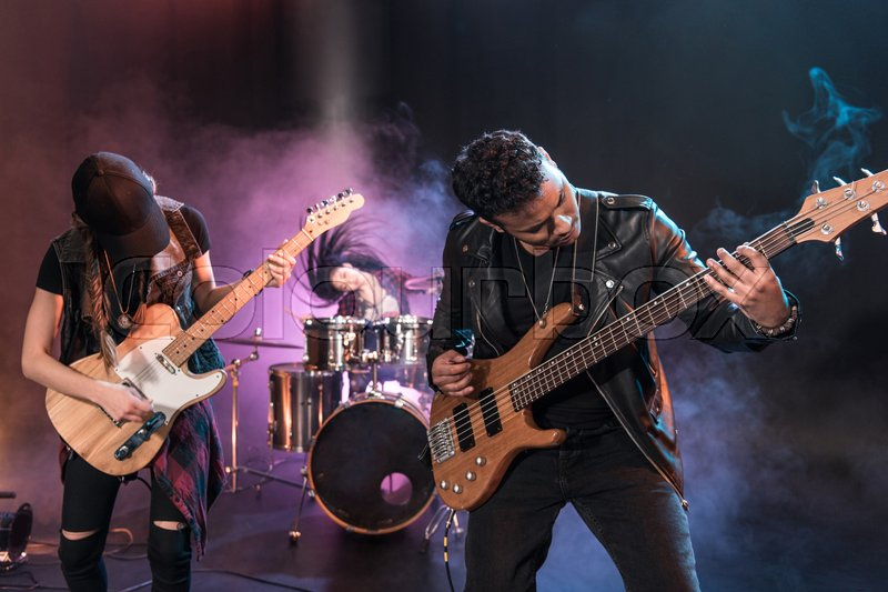 Rock and roll band with electric guitars playing hard rock music on stage, stock photo