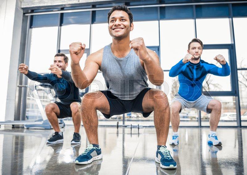 Young men exercising at sports center, stock photo
