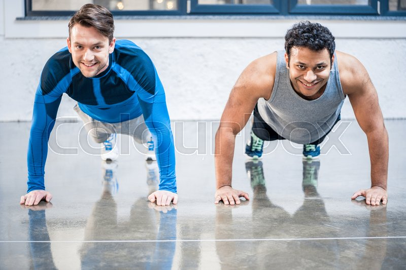 Young men doing push-up at sports center, stock photo