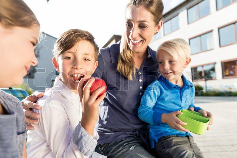 Mother and kids at school having breaktime with apple and lunchbox , stock photo