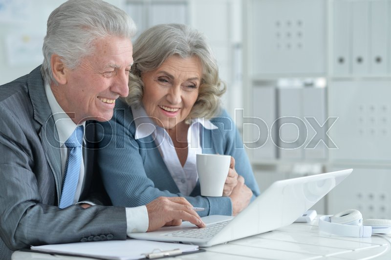 Pair of senior businesspeople working at the office, stock photo