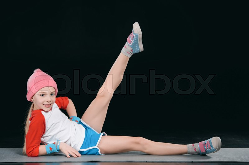 Girl in sportswear exercising isolated on black. acting kids, 11 year old kids concept , stock photo