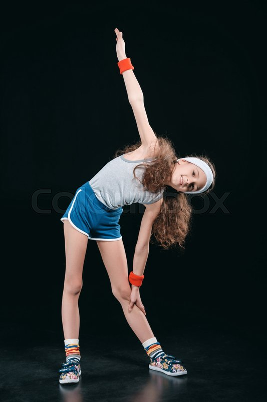 Girl in sportswear exercising isolated on black. acting kids, 12 year old kids concept , stock photo