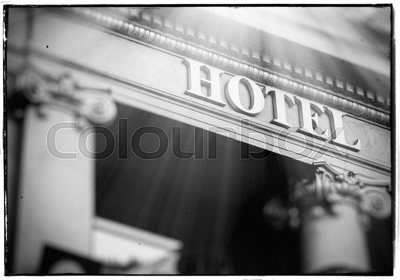 hotel word with sun beam flare coming from the sky majestic letters on luxury hotel with beautiful columns in vintage photo framce stock photo