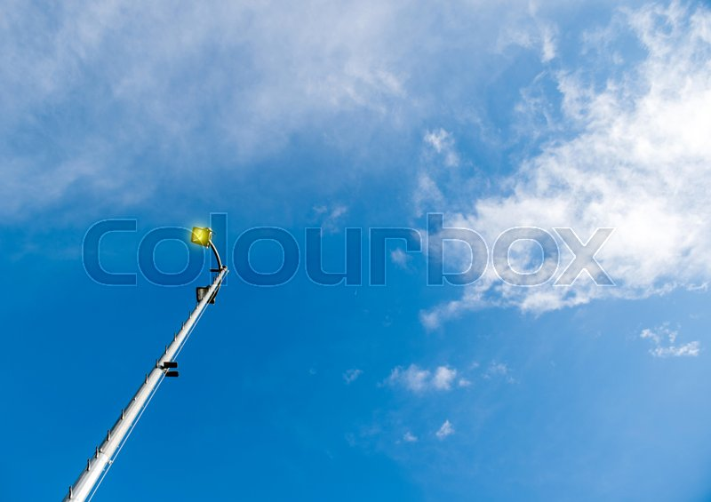 Lighting pole LED street lamp seen from below against blue spring sky with beautiful cloud - yellow pure light coming from the bulb, stock photo