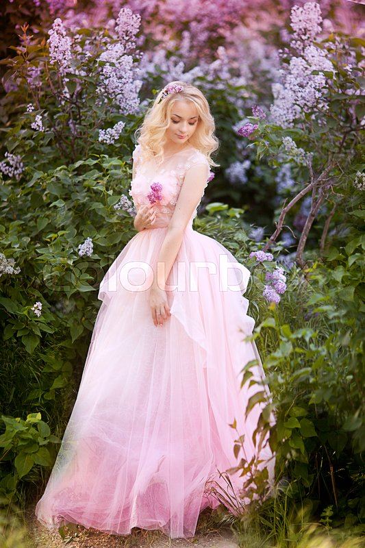 Beautiful woman enjoying lilac garden, young woman with flowers in green park. cheerful teenager walking outdoor. soft light style color.Young girl in beautiful wreath of lilac flowers, stock photo