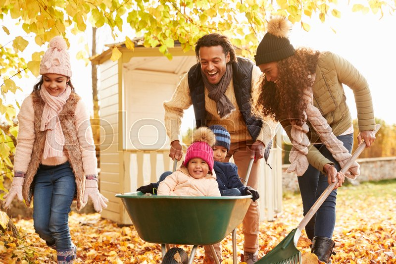 Father In Autumn Garden Gives Children Stock Image
