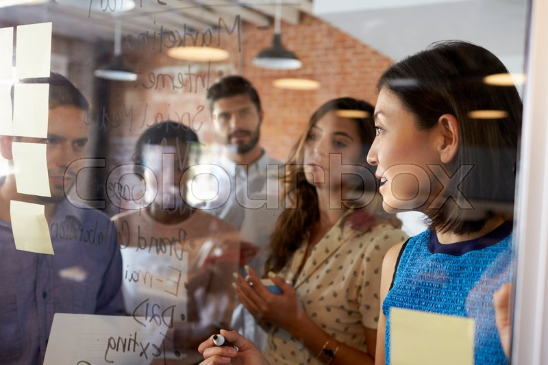 Businesswoman Writing Ideas On Glass Screen During Meeting, stock photo